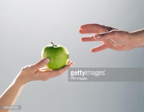 Stock Photo : Woman handing man an apple