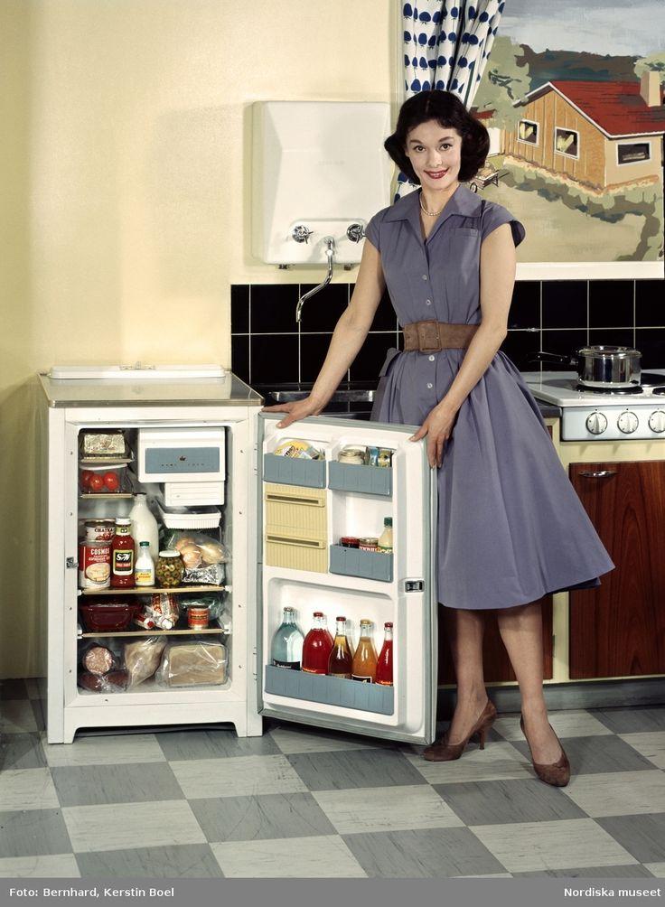 Kvinna i köksmiljö, ca 1958-1962. Kylskåp med öppen dörr, fyllt med matvaror. Foto: Kerstin Boel Bernhard