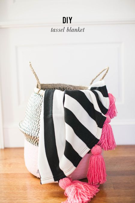 This is one throw you won't want to pack away at the end of winter! Pink tassels and black and white stripes make for the sweetest DIY blanket.