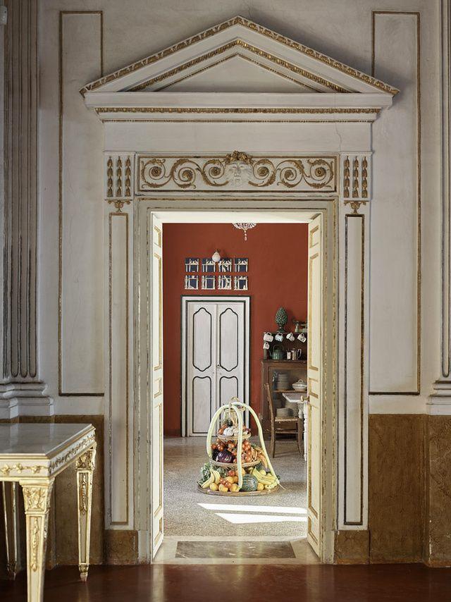 La Villa Valguarnera en Sicile Du grand salon, on pénètre dans la cuisine, pièce à vivre de la famille. Posé au sol, un panier de paille des années 1920 trouvé au grenier sert de porte-légumes et fruits. En fond, un détail d'une fresque d'origine qui entourait le portrait de Marianna Valguarnera, aïeule de l'actuelle princesse.
