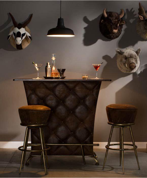 Pon una cabeza (o más) en tu pared y crea tu propia composición animal. El mueble bar y los taburetes de aire retro hacen el resto.