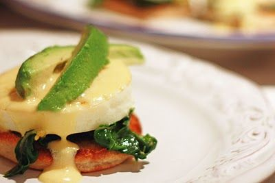 ... egg spoon hollandaise over eggs garnish with avocado slices serve