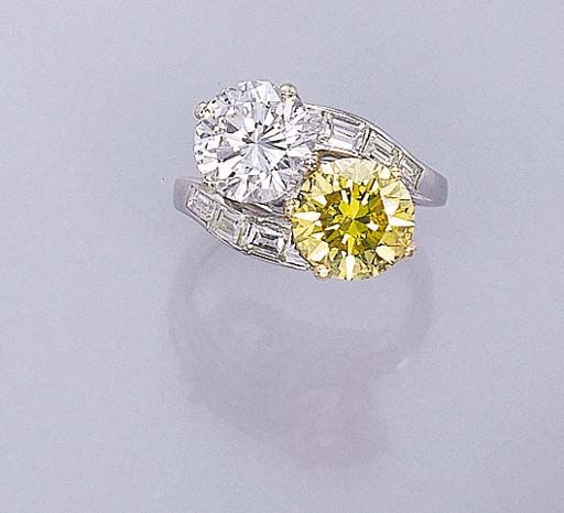 A TWO-STONE DIAMOND AND TREATED YELLOW DIAMOND RING   Of crossover design, set with a circular-cut diamond and treated yellow diamond weighing 3.02 and 3.03 carats to the baguette-cut diamond undulating shoulders and platinum hoop