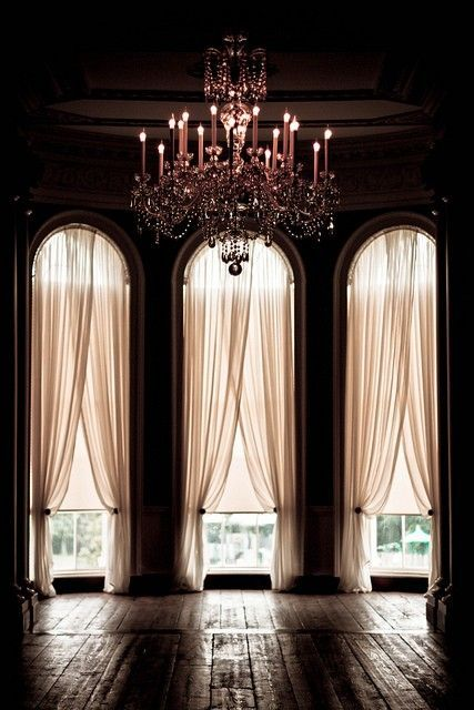 Simple but stunning. Long, elegant curtains skimming hardwood floors and a glamorous chandelier.