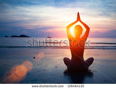 Silhouette young woman practicing yoga on the beach at sunset. - stock photo