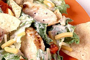 Our taco chicken salad recipe is a party on a plate. Layers of lettuce, nacho chips, cheese, salsa and grilled chicken make your mouth say olé!