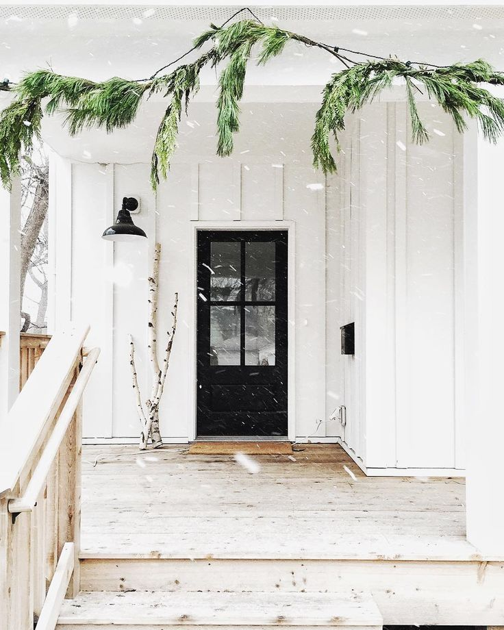 Gorgeous white farmhouse with black front door and simple greenery around the stairs