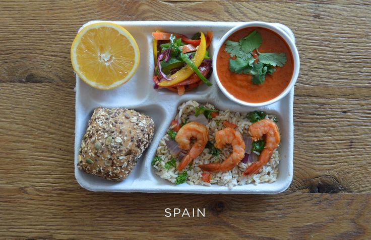 Provided by The Huffington Post School lunch from Spain - Sautéed shrimp over brown rice and vegetables, gazpacho, fresh peppers, bread and an orange.
