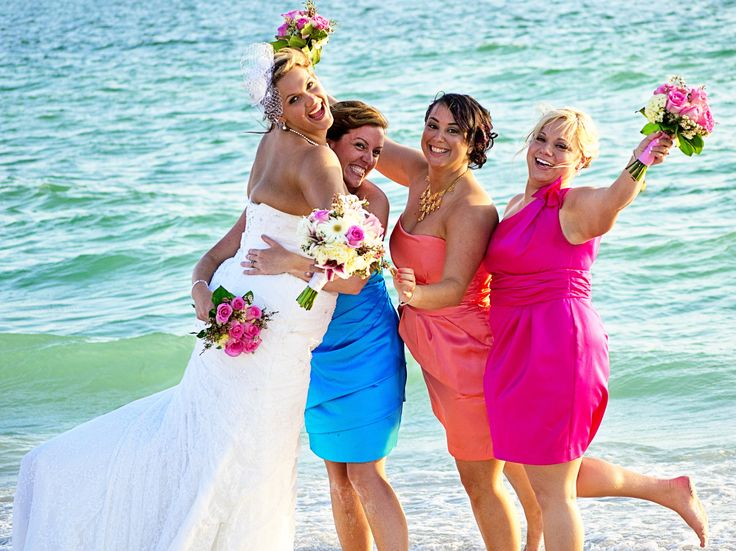 Beach wedding multicolor bridesmaids dresses. Adds a colorful color palette to a tropical beach theme. David's bridal dresses in coral, begonia (pink) and Malibu ( blue).