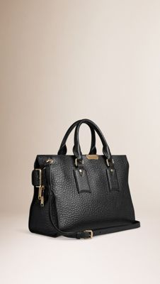 Burberry Medium Clifton in signature grain leather. Inspired by the Heritage trench coat, the design features adjustable side buckles. Discover the women's bags collection at Burberry.com