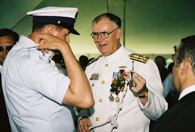 Admiral Loy, retiring Commandant USCG accepting a boatswain's whistle from a PO3 boatswain. May     2002.  Photo by Peter Eikenberry
