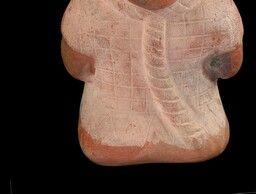 54/ MOCHE - Vase en céramique beige rosé, engobée beige et peinte, représentant un personnage agenouillé, les mains liées derrière le dos et la corde au cou, la coiffure du personnage formant goulot. Chemise à manches courtes. Les jambes ne sont pas indiquées (fond plat). Poignets liés dans le dos. Traits du visage bien dessinés : yeux en amande ouverts, nez proéminent aux narines largement ouvertes. Bouche largement fendue aux lèvres minces. La tête est très grosse par rapport au corps. 26…