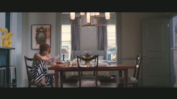 "Jennifer Lopez's Brownstone in ""The Back-up Plan"". Chandelier and chairs. Upholstered headboard between windows with long curtains."