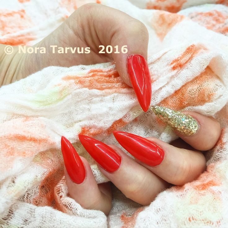 Super luxurious long, sharp and pointy acrylic nails decorated with some golden glitter and bright red gel polish.