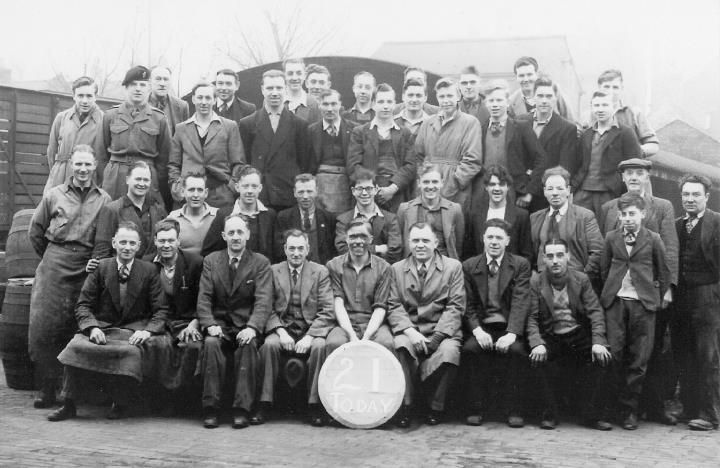 This group photograph shows fellow coopers following the 'trussing in' ceremony of Peter Atkin, at Bass Brewery, Burton upon Trent, on 12th April, 1952, looking forward to a celebration pint of best bitter. On the left of Peter is his father Allen, who was the cooper's storekeeper, and on his right is Walter Harrison, who was his tutor during his six year apprenticeship.