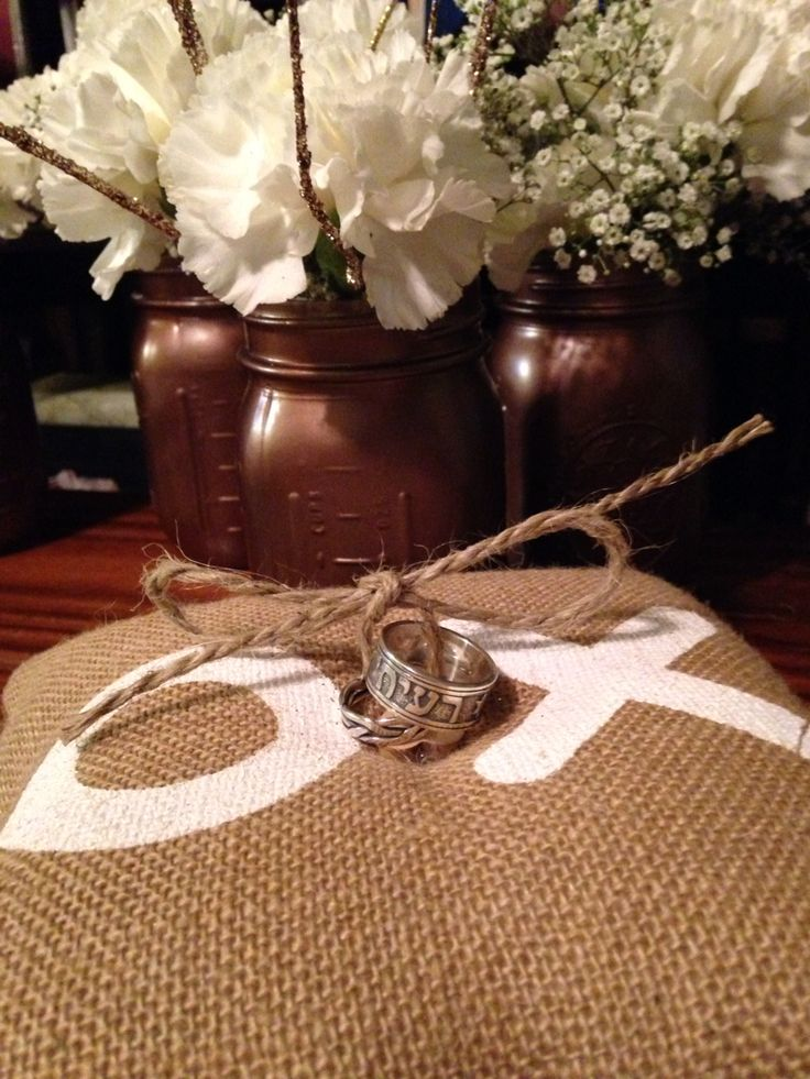 Wedding rings on ring bearer pillow. The mason jars were spray painted gold and filled with real carnations and gold sticks from Hobby Lobby