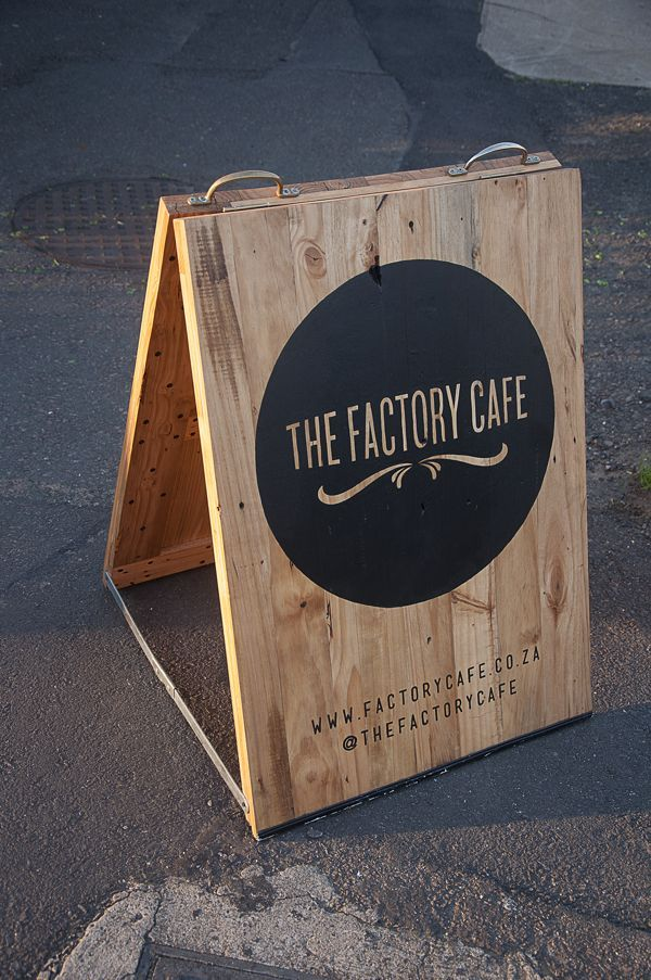 An A-frame sign made from old pallet wood, designed for 'The Factory Cafe' in Durban, South Africa.