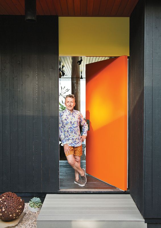 """Doonan stands next to the front door.  """"We have flamboyance, and we're not inhibited about anything. Gray Organschi gave [the house] that intellectual rigor needed to make it beautiful. We were well matched.""""—Resident Simon Doonan"""