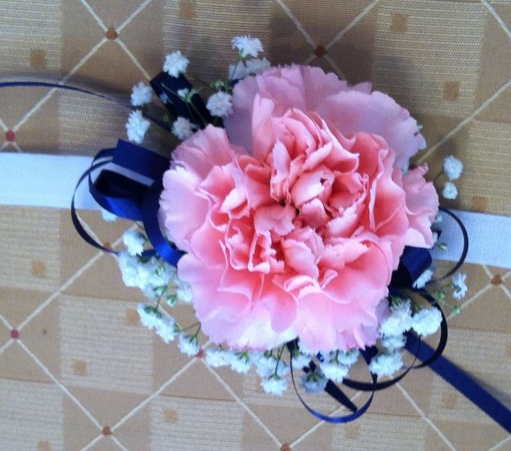Wrist corsage of a pink carnation with accents of babys breath