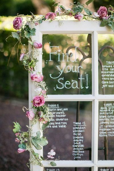 Seating chart written out on a window pane with floral accents