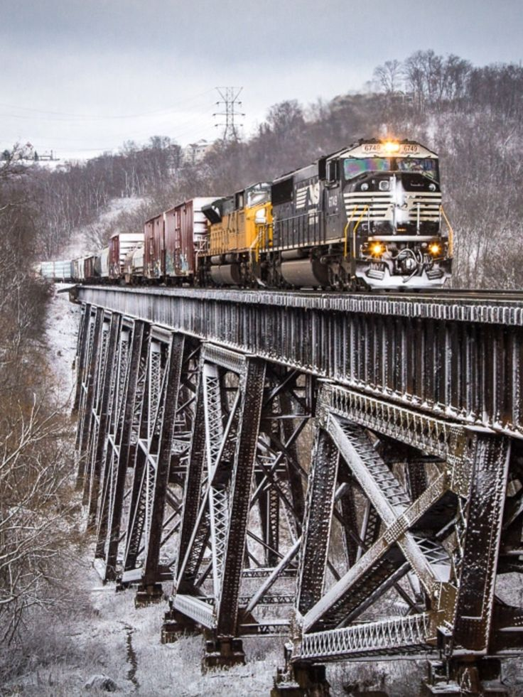 Snow from earlier in the day coats the ground while a pair of EMD products lead Norfolk Southern mixed freight 113 across the 1st Trestle in Ludlow, Kentucky. Photo by Brandon Townley. Source Flickr.com