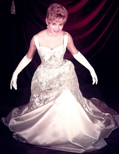 Brigitte Bardot posing in a Balmain gown which she wore at the meeting with the Queen Elizabeth in 1956
