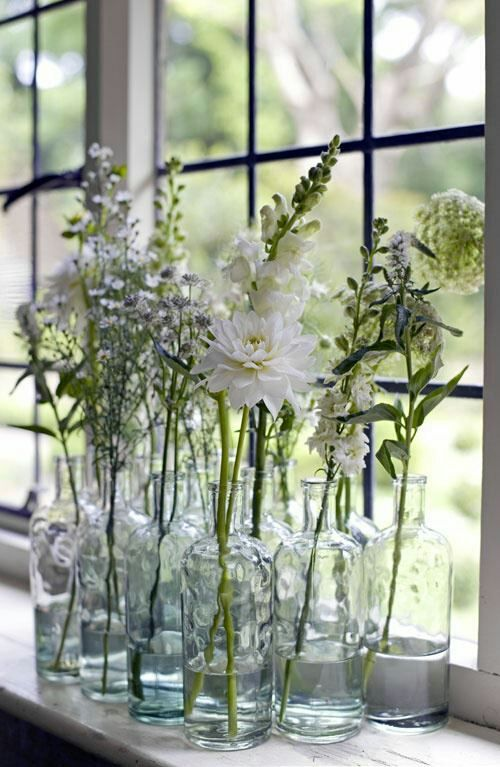 Wildflowers in a grouping of bottles on a windowsill