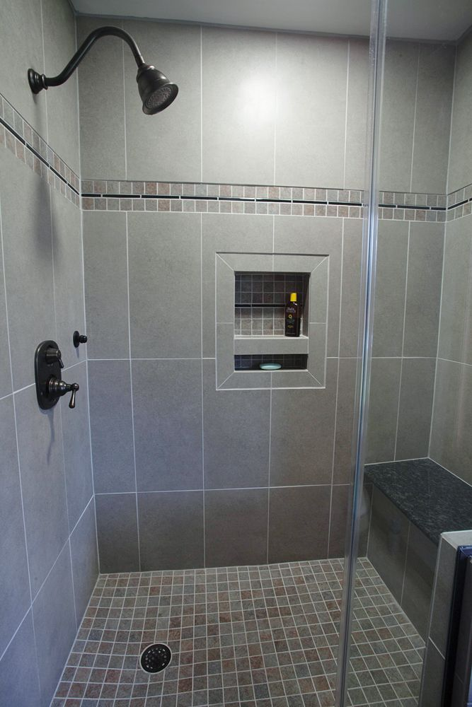 Custom built tile shower with granite bench, accessible niche, and tile floor installed to replace carpet.