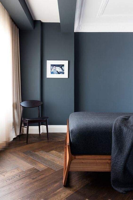 Dark gray matte wall paint color bedroom with a dark hardwood herringbone floor, walnut wood midcentury bed frame, black wool and cotton bedding, black painted accent side chair, floor to ceiling white curtain, and framed and matted photograph.