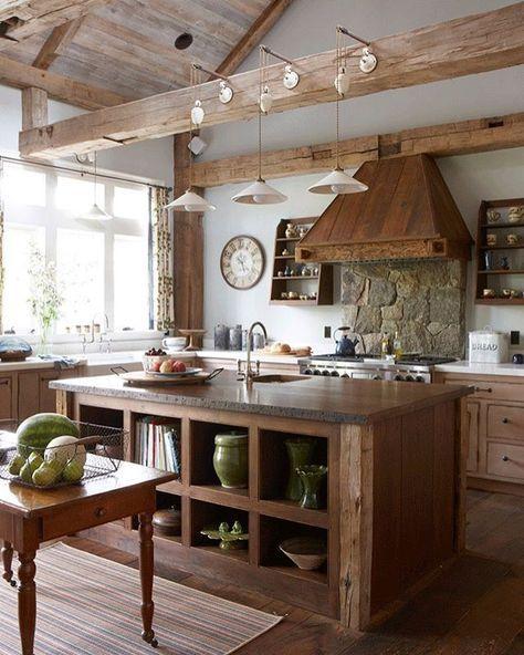 Gorgeously rustic kitchen with exposed beams, wood range hood and stone backsplash.