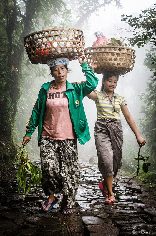 Mother & Daughter from Bali carrying items in large baskets on their heads.