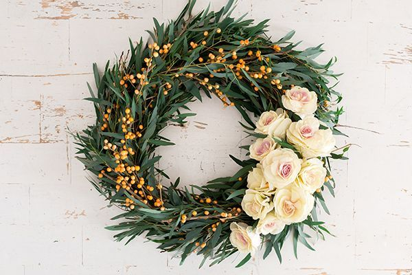 DIY holiday wreath with fresh greens and roses.