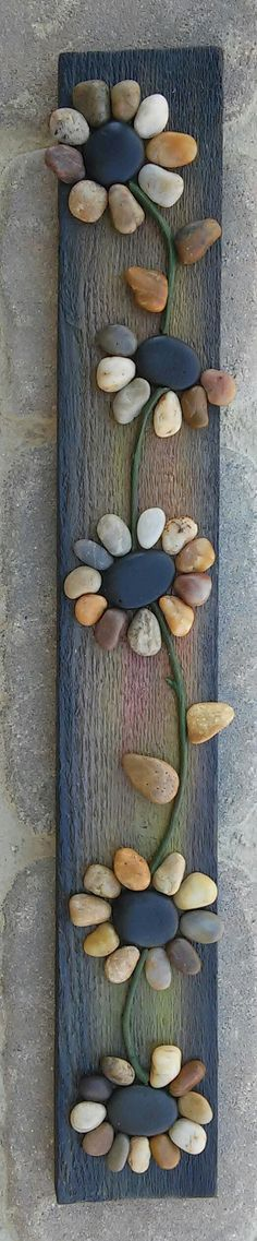 Pebble/rock art depicting a string of flowers (all natural materials including reclaimed wood, pebbles, twigs)