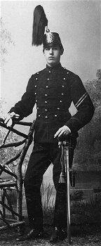 Artillerist i Attila m/1872 med svart snörliv. Huvudbonad käppi m/1880.