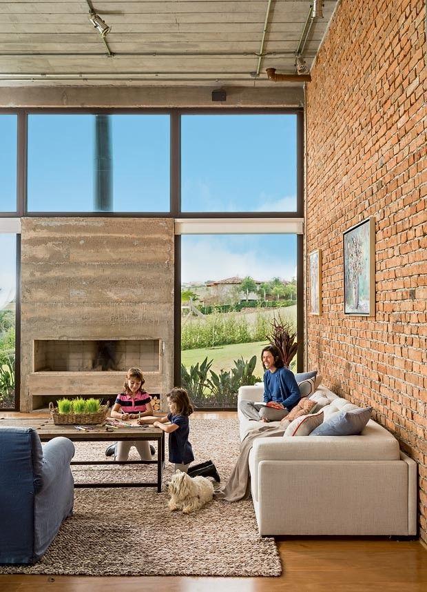 Sala de estar | Ao redor da lareira de concreto aparente, os painéis de vidro temperado de 10 mm deixam ver a paisagem. A proprietária Laura está no sofá da Artefacto com manta e almofadas da Empório Beraldin, Celina Dias e Dialma Brown. (Foto: Edu Castello/Editora Globo)