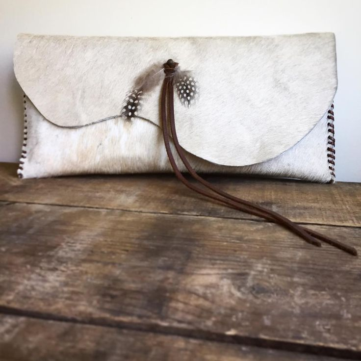 This little cowhide leather stunner is the perfect accessory to hold your necessities! The contrast stitching and beautiful feather + leather tassel are the details that make this handheld bag extra s