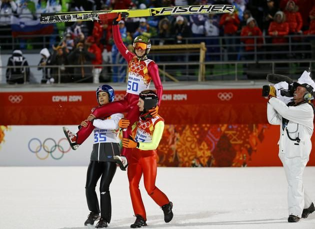 Kamil Stoch of Poland celebrates with compatriots after the final ...