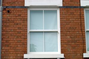 Traditional sliding wooden sash window with cords and weights.