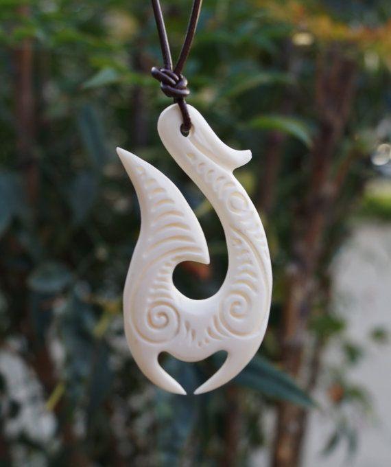Hand carved maori hei matau and koru cow bone pendant on
