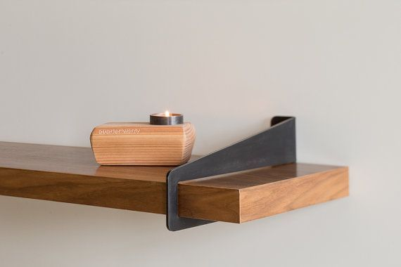 A simple piece of laser cut and formed steel cantilevers off your wall and accepts a standard 2x10 wood plank to create a shelf width of your choosing (will support a shelf up to 6 feet wide):
