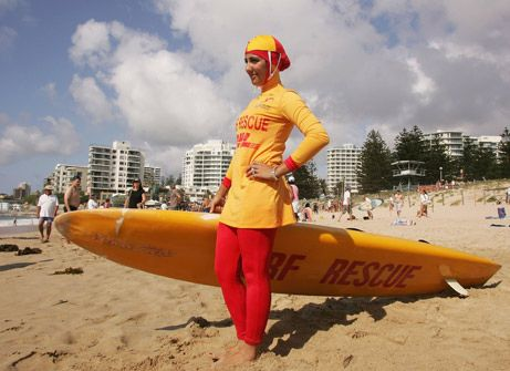 """Sydney, Australia, February 4, 2007—A year after vicious race riots took place there, Sydney's Cronulla Beach became a runway of reconciliation with the unveiling of the """"burqini."""" The two-piece, body- and head-concealing swimsuit is seen here on 20-year-old lifeguard Mecca Laa Laa.  Reportedly endorsed by the Australian Islamic Council and Australian muftis, the swimsuit allows female Muslim lifeguards to serve on the sand while conforming to strict religious requirements.  Cronulla Beach…"""