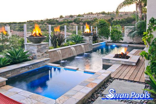 Geometric swimming pool and spa installed with fire bowls and a fire pit entertainment area in Newport Beach, California.