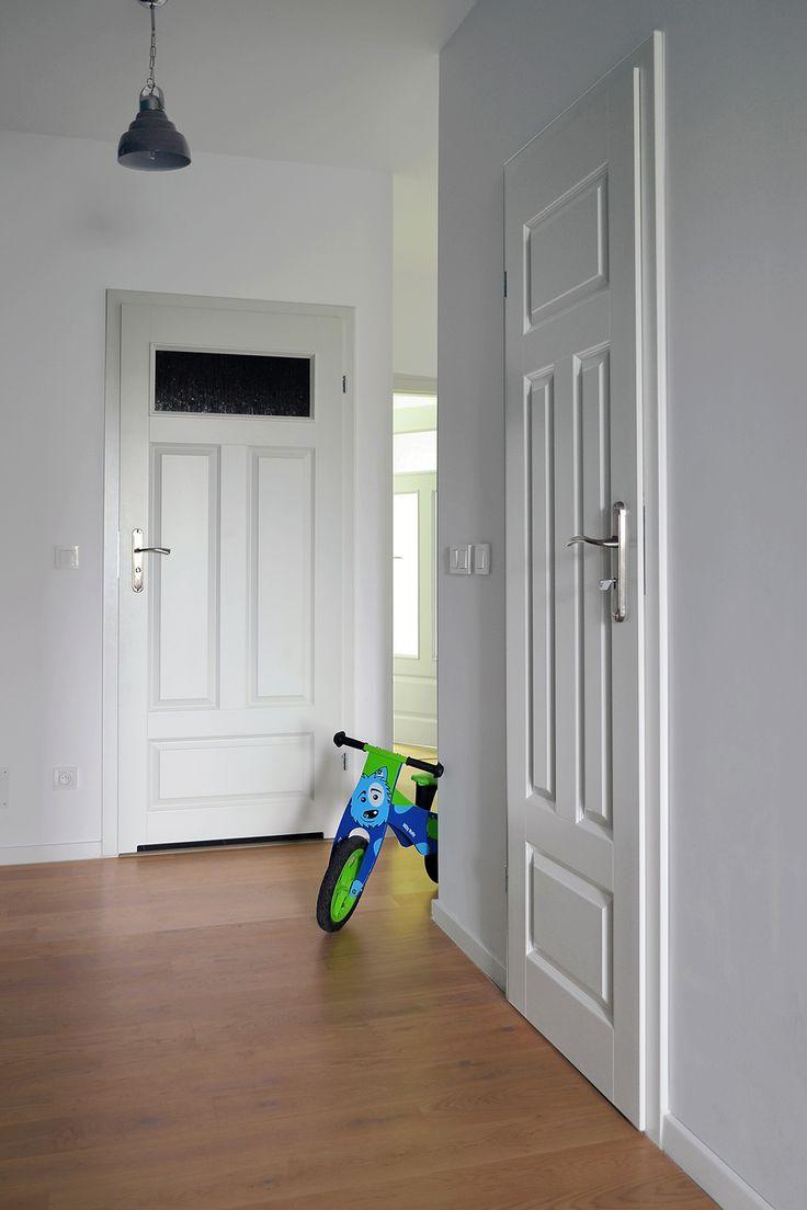 Biały, minimalistyczny korytarz. Na takim tle ładnie wyróżnia się szara lampka.