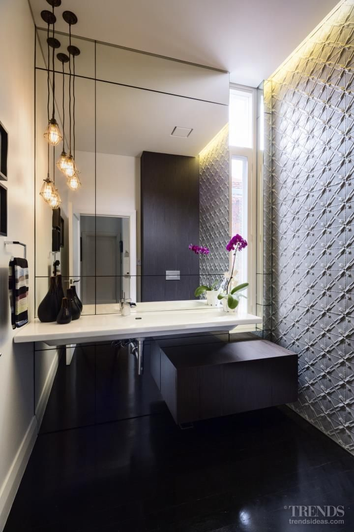 Pressed metal wall is standout feature in this sleek powder room
