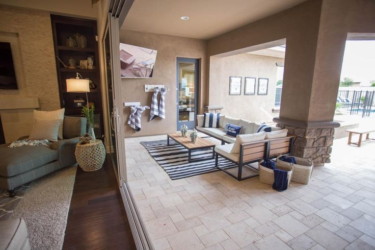 Broad sliding doors connect the indoor and outdoor living spaces of this transitional home. A covered patio has the perfect spot for entertaining, with a view to the pool beyond.