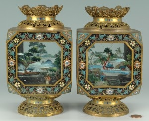 """Pair Chinese cloisonne painted table lanterns with four reverse painted glass panels depicting various landscape scenes and cloisonne frames and corners. Pierced bronze metal tops and bases. Most likely missing the plinths and shafts originally supporting the lanterns. 7-1/2"""" H. 20th century. Condition: Some oxidation to metal. Overall very good condition."""