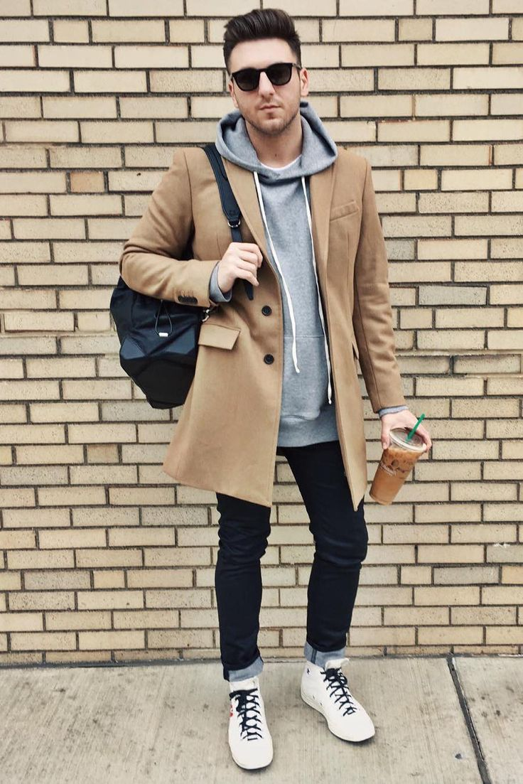 Stephen Weisbrod looks casual and cool in a gray hooded sweatshirt, dark wash jeans and white high top shoes. He adds an extra layer of warmth with our men's camel topcoat | Banana Republic