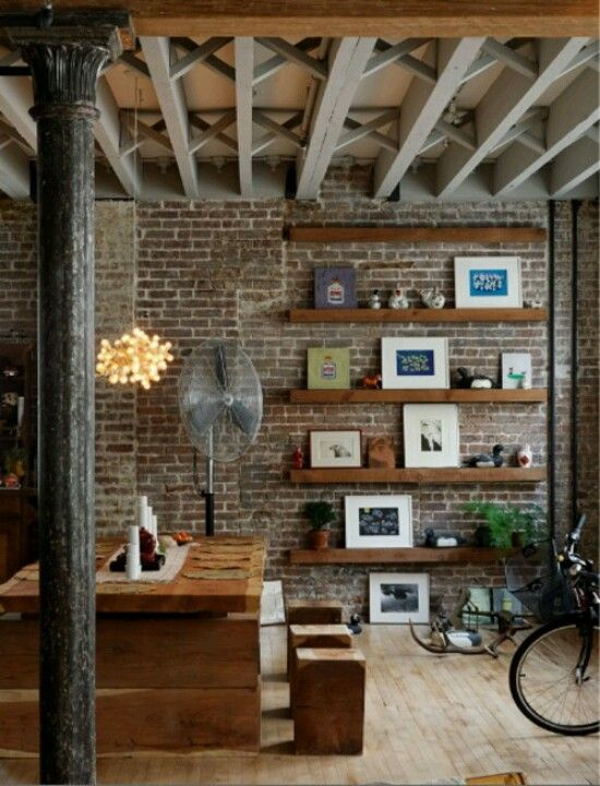 A brick accent wall ( fauxe panels would work) with shelving dig it would be good one wall coming in from front door