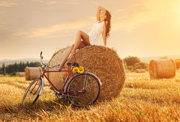 Fashion photo, beautiful woman sitting on a bale of wheat, next to the old bike …  Jordan Feddema