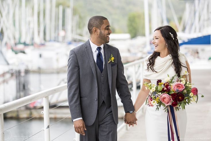 A happy, natural moment between a mixed race bride and groom, laughing and walking down the deck at Bluffer's Park Marina, with boats and the Bluffs in the background. Bluffers Park Restaurant, Scarborough Bluffs Wedding #sweetheartempirephotography http://sweetheartempire.com/blog/images/scarborough-bluffs-wedding